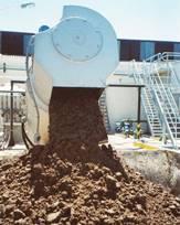 Lodo biológico deshidratado sale de una prensa de tornillo marca HUBER
